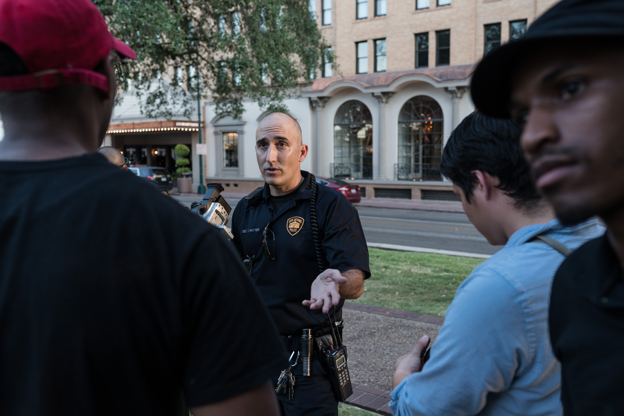 Mike Lowe, 36, and Johnathan Jones, 24, talk to Det. T.Patton, 46, about videotaping the protest. Photo by Anthony Francis.