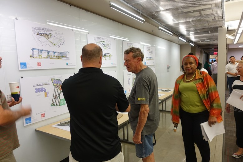 Gloria Ray, chairwoman of the Alamo Colleges Citizens Advisory Committee, walks by Westfort neighborhood residents studying renderings at WestEast Design Group's offices at Pearl Thursday. Photo by Robert Rivard.