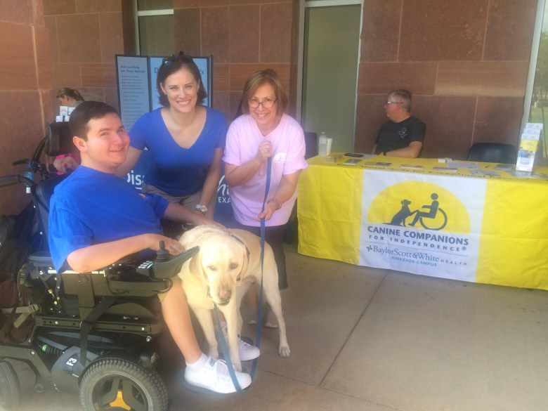 (From left): Corey Brooks, Maureen Caspers, and Ana Brooks of Canine Companions for Independence pose for a photo with Corey's service dog, Obie.  Photo by Camille Garcia.