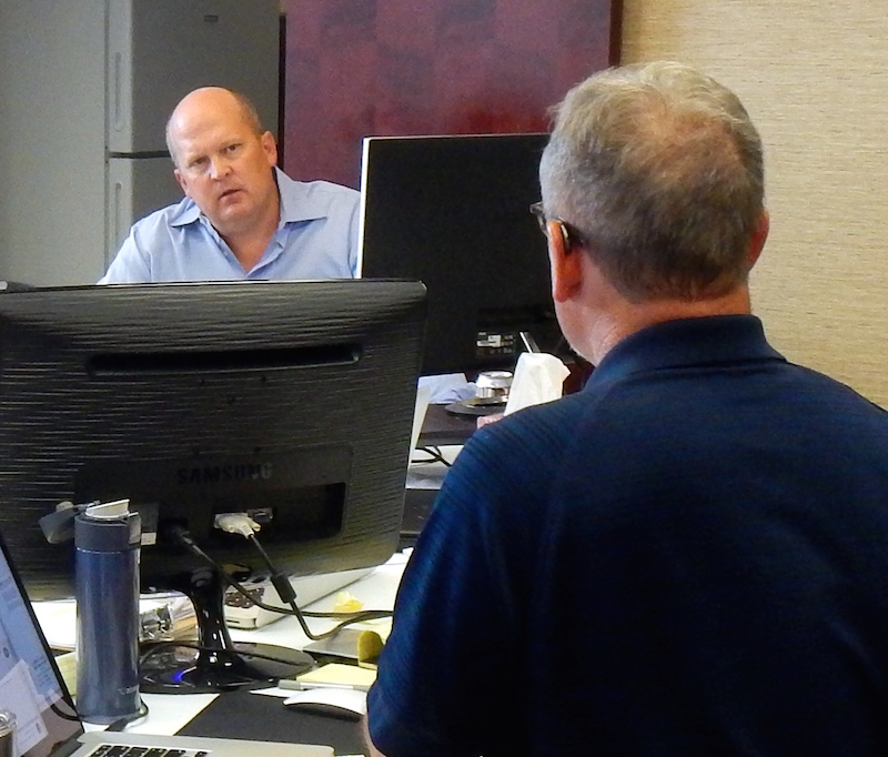 """Mikal Watts (left) and Mike McCrum strategize in the """"war room"""" prior to their trial in GUlfport, Miss. Photo by Desi Canela."""