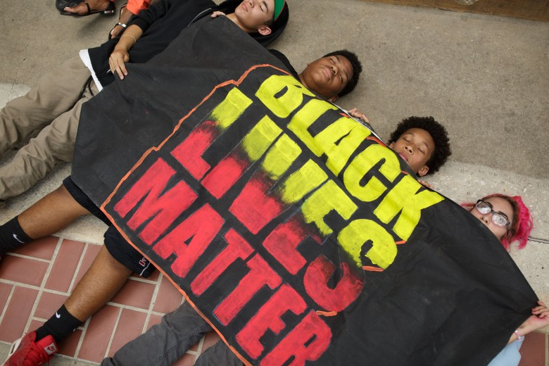 From left: Ian, 15, Artrand, 15, Casai, 14, and Ahoilani, 14, lie on the ground during the die-in on the steps of City Hall. Photo by Scott Ball.