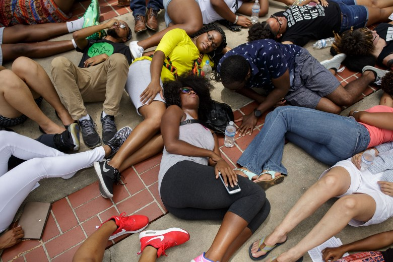 Protestors lie on the pavement in front of City Hall during the die-in. Photo by Scott Ball.