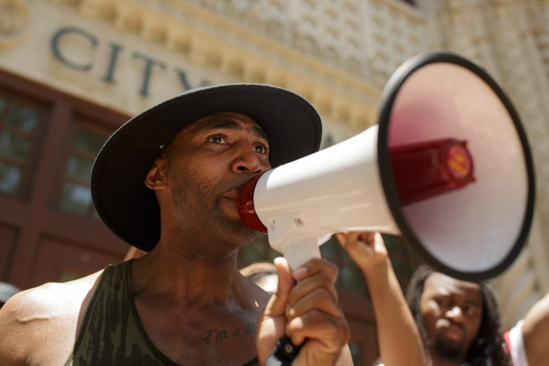 """Organizer Mike Lowe with SATX4 shouts, """"Stand up because Marquise Jones can't stand up,"""" from the steps of City Hall with tears in his eyes. Photo by Scott Ball."""