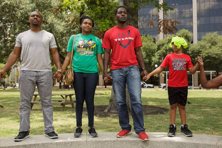 From left: Robert Myers, Spendrika Farwell, Vaughn Fontenette, and a child hold hands forming a circle around the confederate statue in Travis Park. Photo by Scott Ball.
