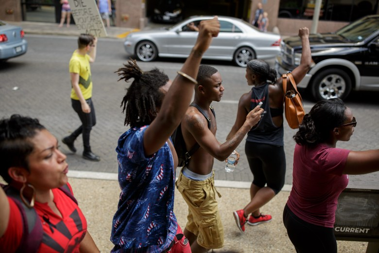 Members of the demonstration walk south on Navarro Street heading towards City Hall. Photo by Scott Ball.