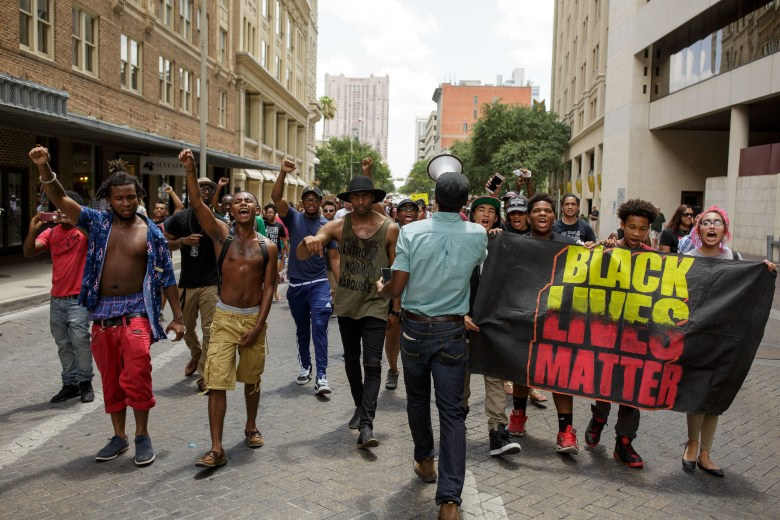 The marching protest led by Mike Lowe and Johnathan-David Jones (center) walks down Commerce Street in the direction of City Hall. Photo by Scott Ball.