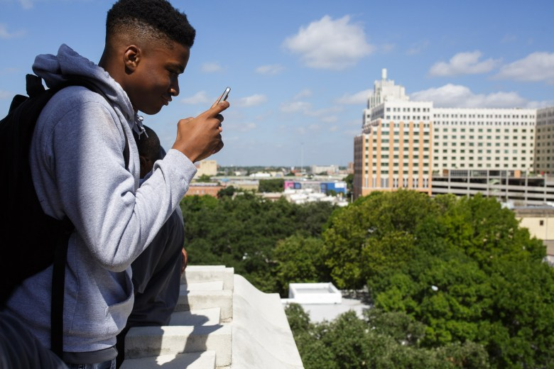 An Eastside Dreamer takes a photograph of downtown San Antonio from a balcony located at City Hall. Photo by Scott Ball.