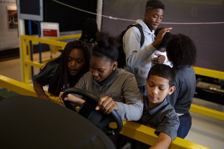Eastside Dreamers get behind a demonstration steering wheel at the Toyota Motor Manufacturing Visitor Center. Photo by Scott Ball.