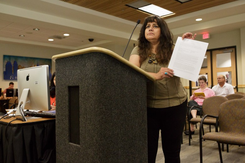 Maria Torres holds up a document protesting the development behind Mission Concepción.  Photo by Scott Ball.