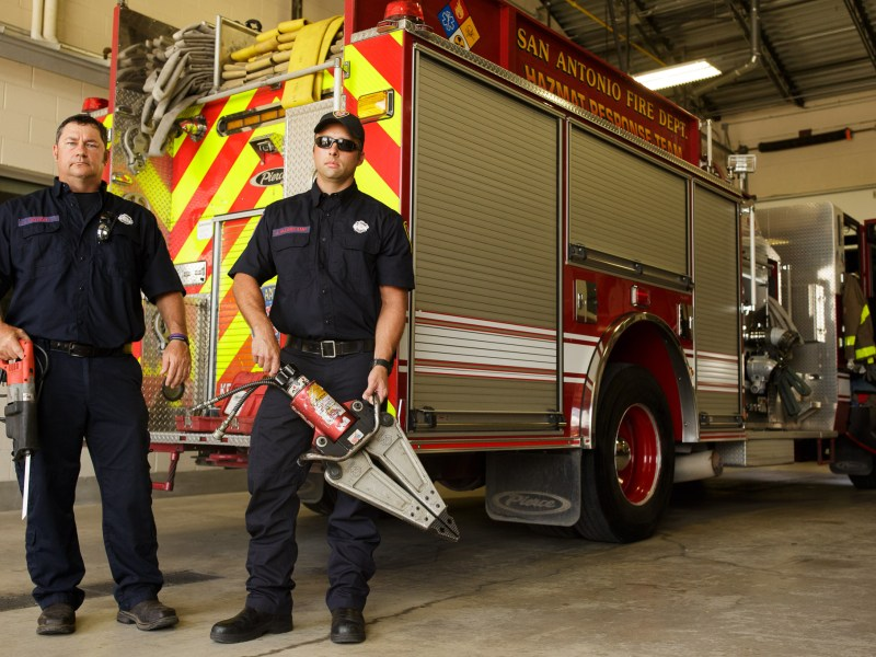 SAFD Engineer/Paramedic Trey Votion (left) and SAFD Engineer James Allerkamp stand for a photo at San Antonio Fire Department Station 1 while holding tools used to save the life of Gavin Claybourn. Photo by Scott Ball.