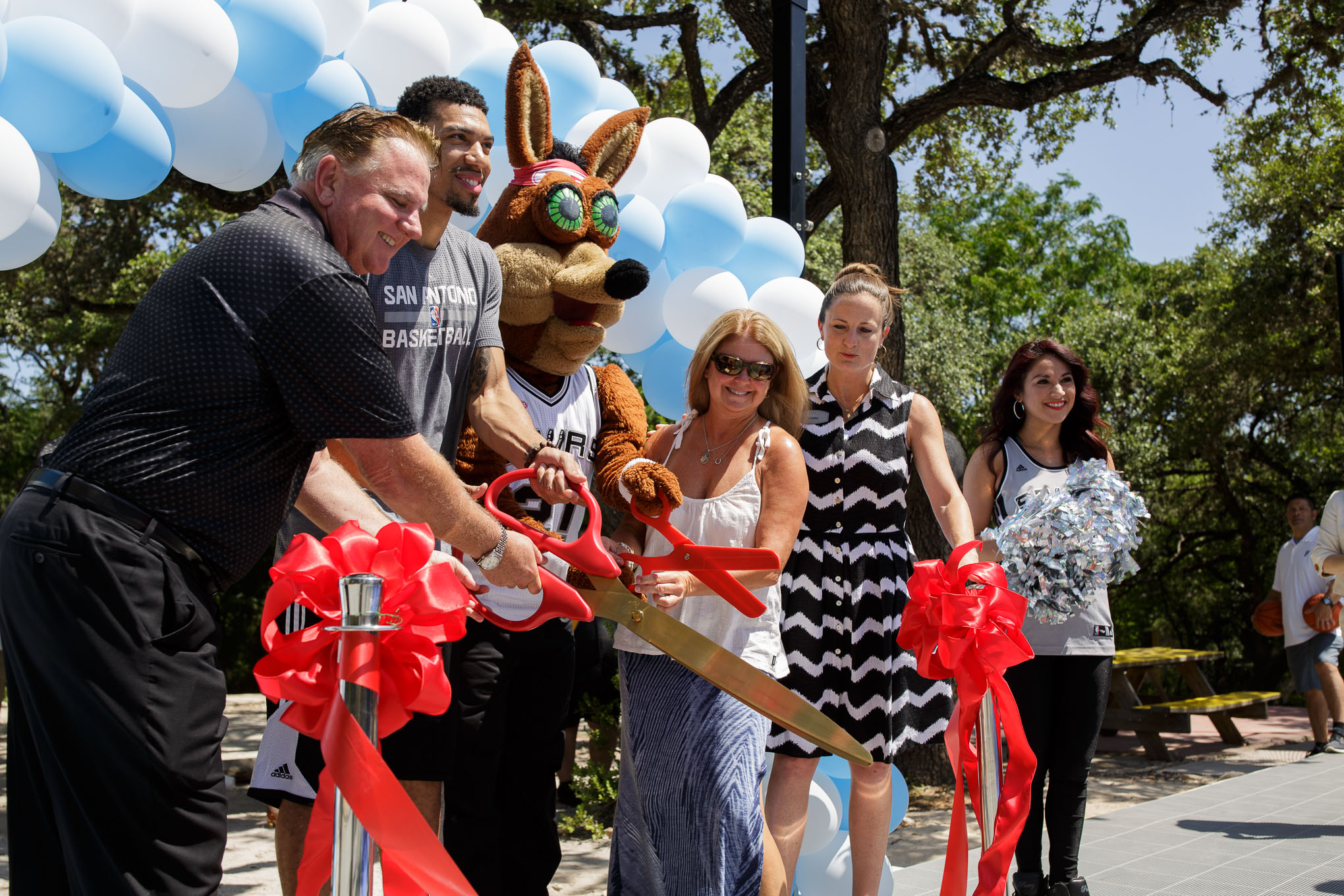 (left to right) Cory Basso, Danny Green, Spurs Coyote, Susan Moulton, and Laura Dixon cut the ribbon unveiling the newly installed basketball court at The Children's Shelter Residential Treatment Center. Photo by Scott Ball.