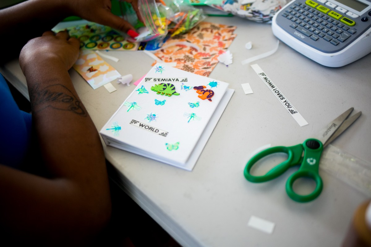 A Seton Homes mother works on a booklet for her child. Photo by Kathryn Boyd-Batstone.