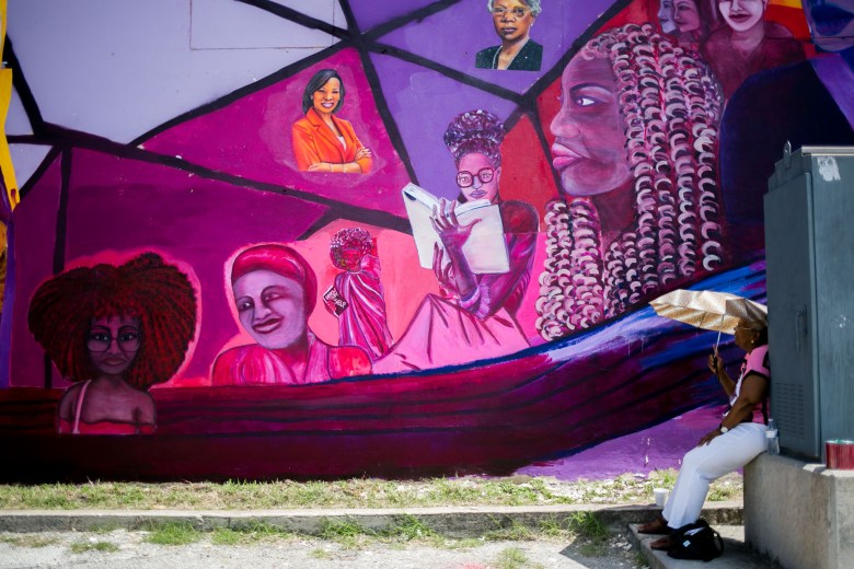 San Antonio Chapter of the National Association for the Advancement of Colored People President Ethel Minor's daughter looks up at the mural which features her mother. Photo by Kathryn Boyd-Batstone.