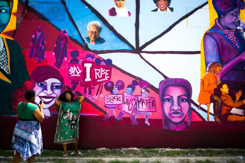 Martinez Street Women's Center Staff Members Janee Eady and Kara Jackson take photos in front of the new mural. Photo by Kathryn Boyd-Batstone.