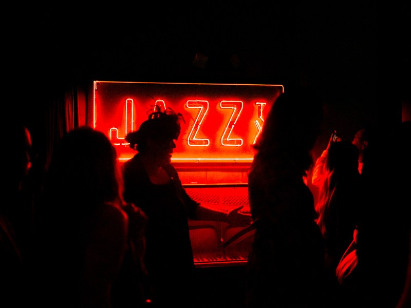 The Jazz, TX logo is illuminated in red neon lights at the entrance of the speakeasy style space. Photo by Kathryn Boyd-Batstone.