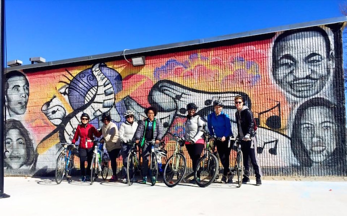 Black Girls Do Bike participants take a break from their ride in front of an Eastside mural. Photo courtesy of Tamisha Johnson.