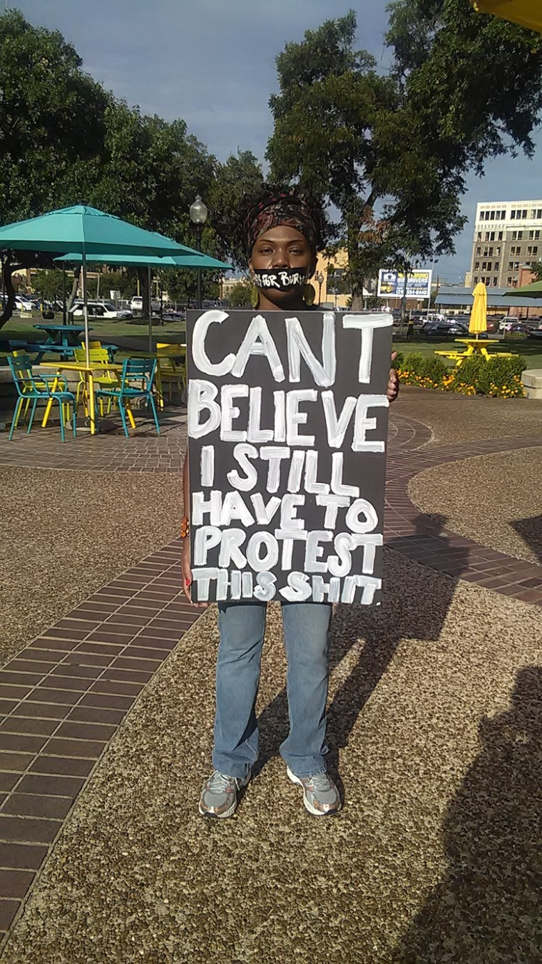 A young woman in the #blacklivesmatter rally holds up a sign. Photo by La Juana Chambers.