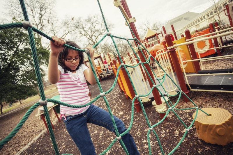A young girl climbs on ropes at a playground. Photo courtesy of iStock.