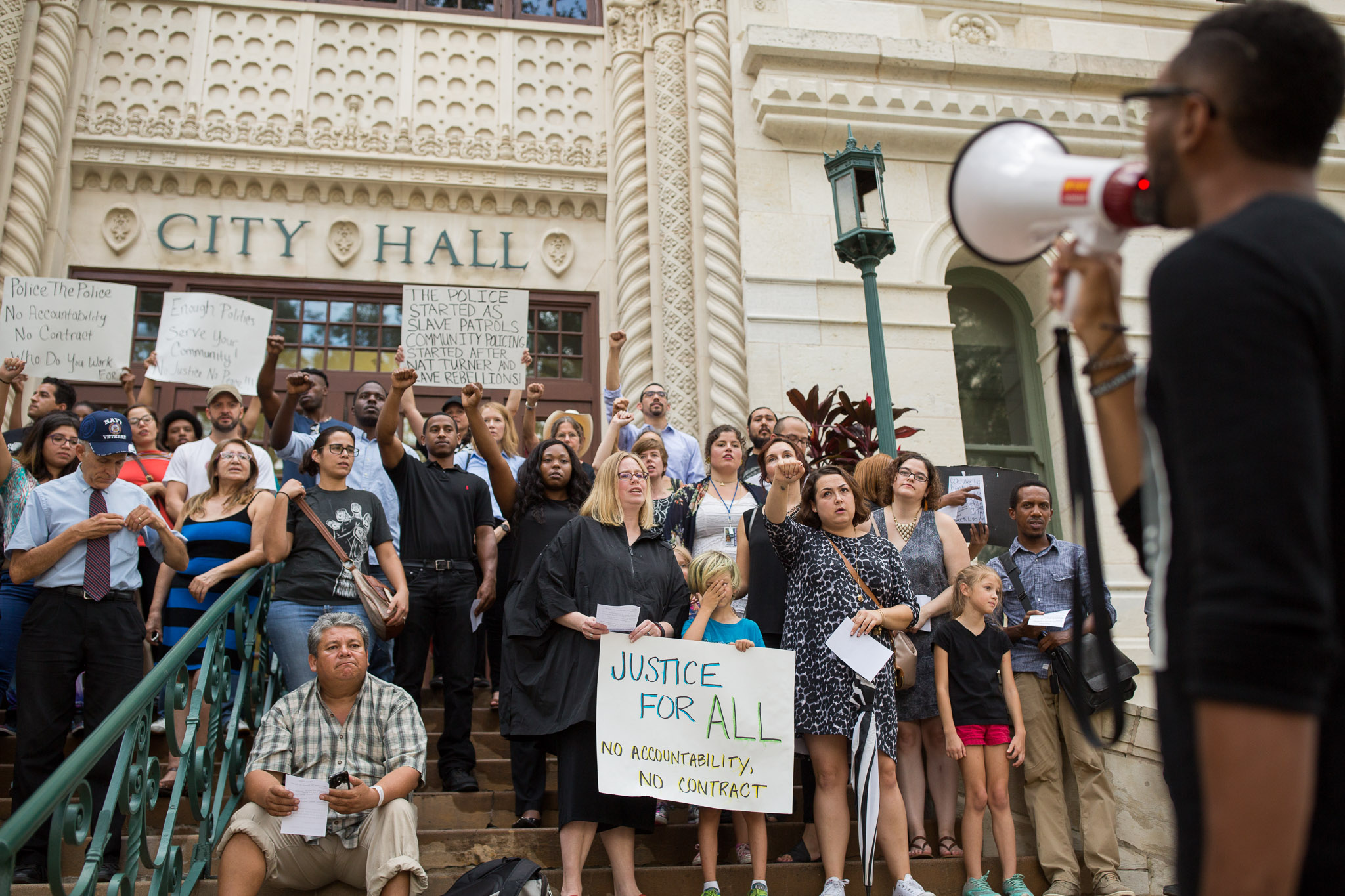 Mike Lowe (right) chants with members of the Black Lives Matter movement on the City Hall steps. Photo by Scott Ball.