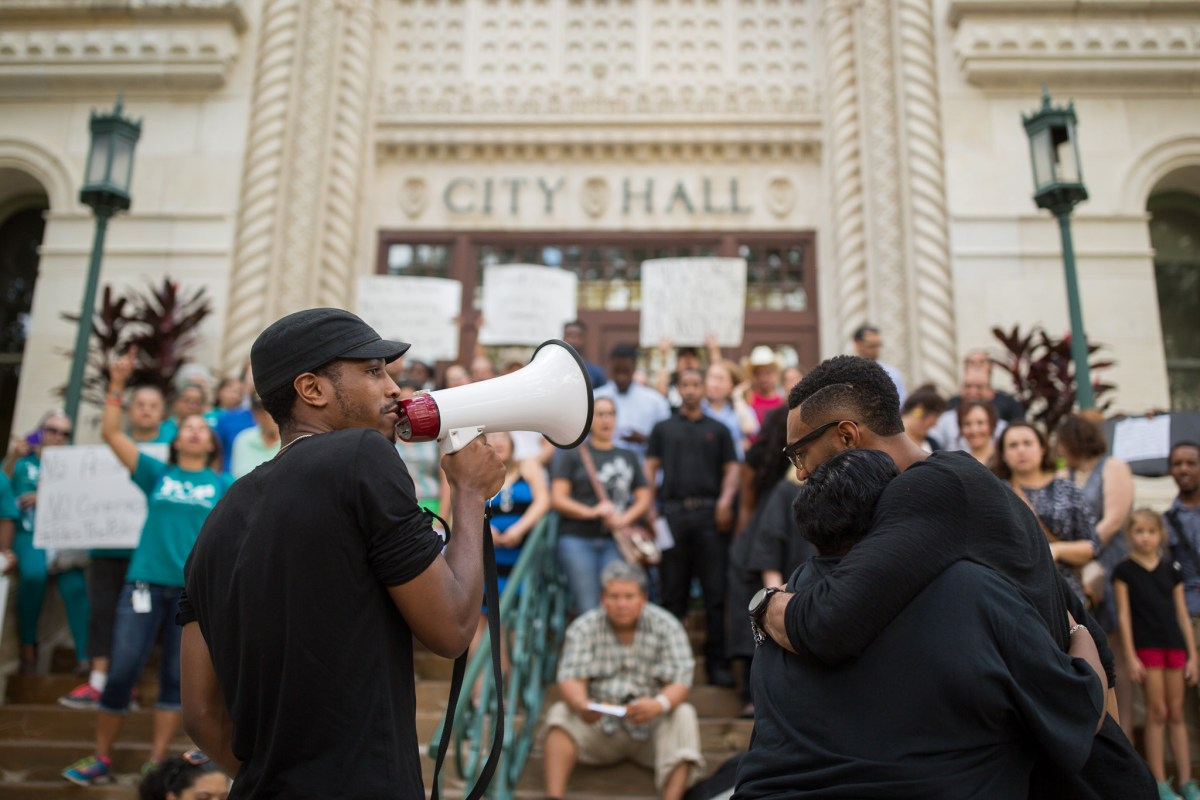 (right) Activist Johnathan-David Jones chants as Debbie Bush and Mike Lowe (right) embrace. Photo by Scott Ball.