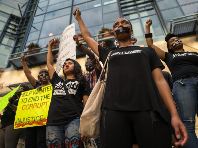 Black Lives Matter activist hold up their fists in front of the San Antonio River Walk. Photo by Scott Ball.