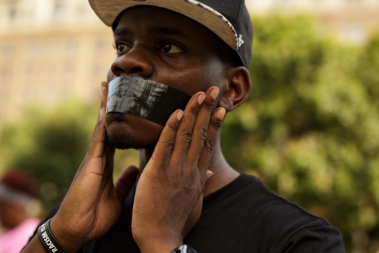 Activist Jeff Wallace adheres tape over his mouth. Photo by Scott Ball.
