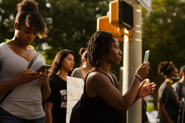 Mary Kay Johnson records video on her cellphone as the protest moves on. Photo by Scott Ball.