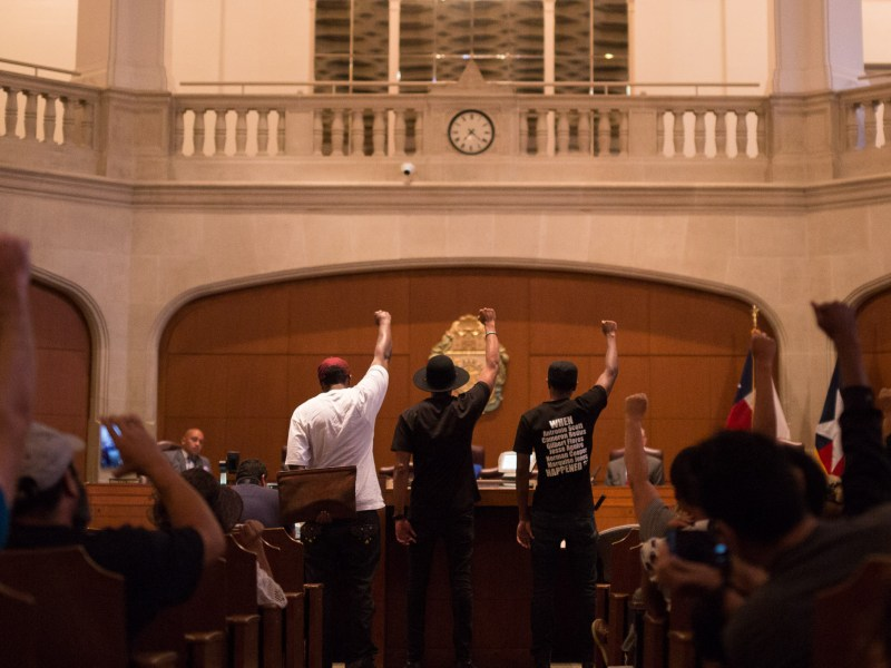 """Local activists raise fists into the air as chants of """"Black Lives Matter"""". Photo by Scott Ball."""