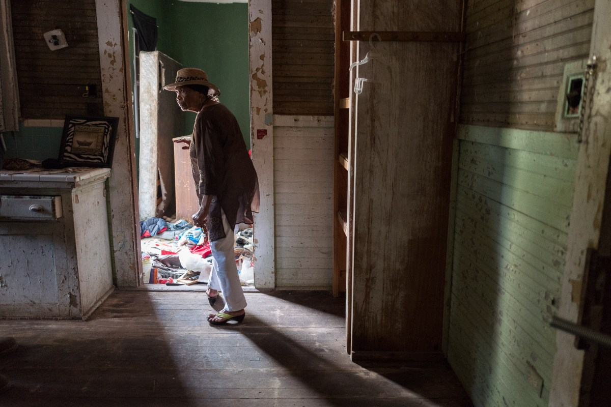 Ethel Jewel Dillard walks through the kitchen of her former house for one last time. Photo by Scott Ball.