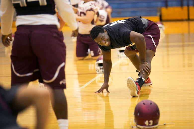 Linebacker Julian Turner and the Trinity football team stretches in the gym because of the rainy weather. Photo by Kathryn Boyd-Batstone.