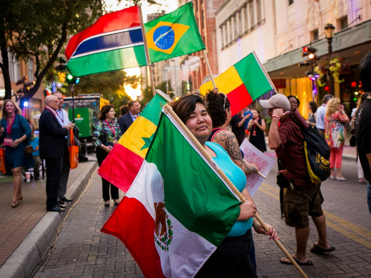 People bear their country's flags as part of the East Houston Street parade. Photo by Kathryn Boyd-Batstone.