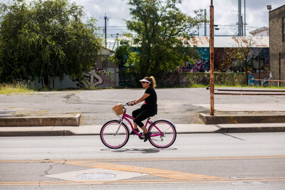 A woman rides her bike down to Mahncke Park along Broadway Street. Photo by Kathryn Boyd-Batstone.