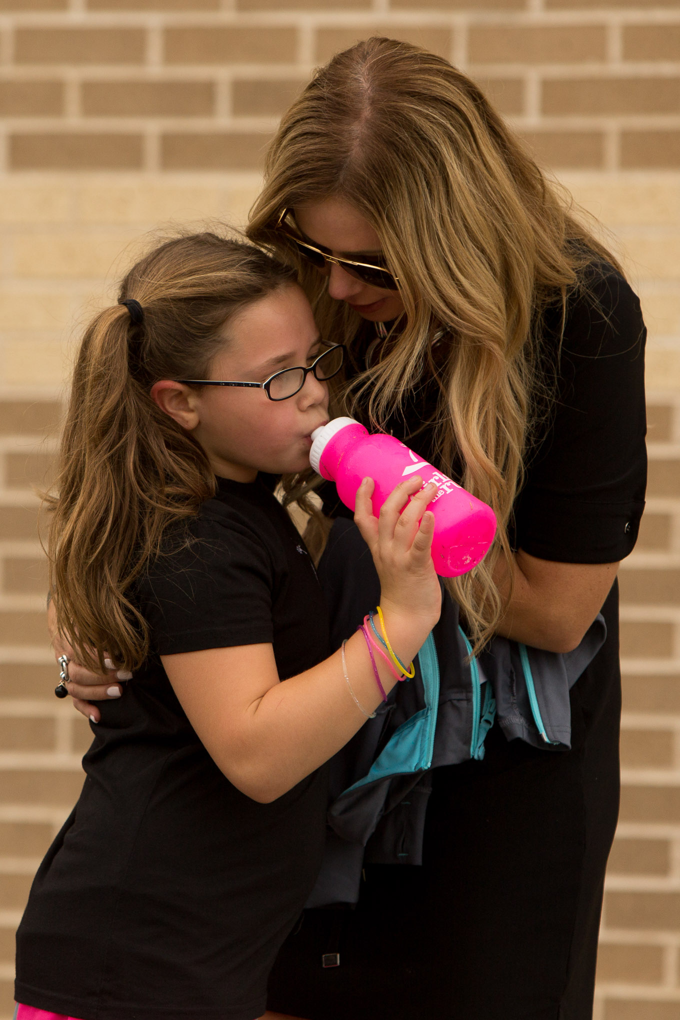 Ava and her mother Traci Lopez share a moment after Ava's run. Photo by Scott Ball.