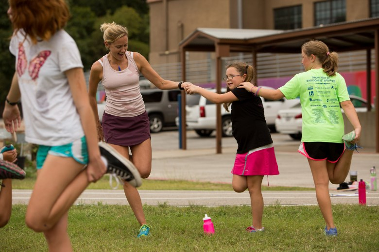 Following laps Ava stretches with her coach Andrea Duke and fellow classmates. Photo by Scott Ball.