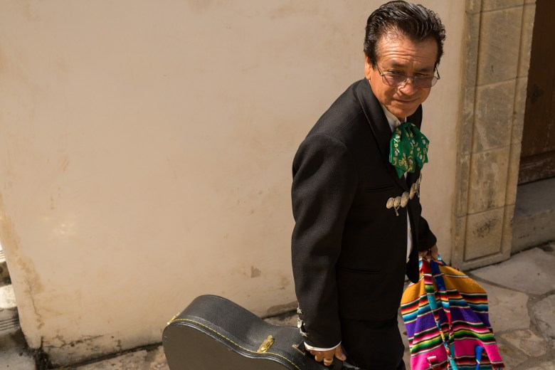 Guitarist Ignacio Piña leaves San Fernando Cathedral following his performance during the ceremony. Photo by Scott Ball.