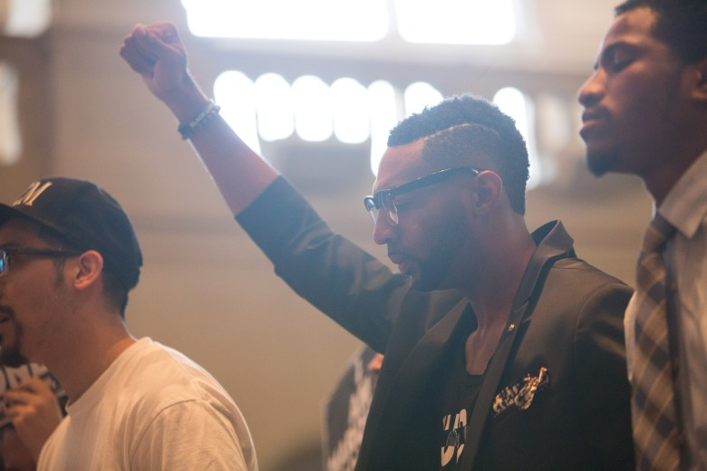 Activist Mike Lowe raises his fist in the air before the voting of the proposed Police Union Contract. Photo by Scott Ball.