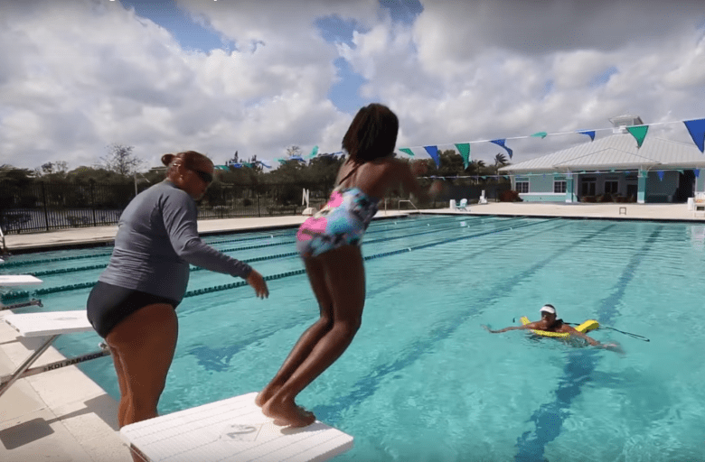 A SWIM Central student jumps off a diving board as part of free water safety lessons.  Photo courtesy of Salud America!