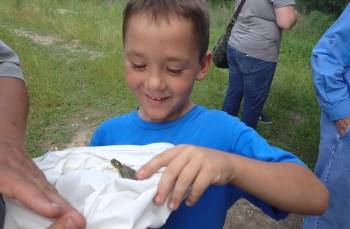 A young visitor meets a Texas Cooter river turtle. Photo courtesy of Cibolo Nature Center and Farm.