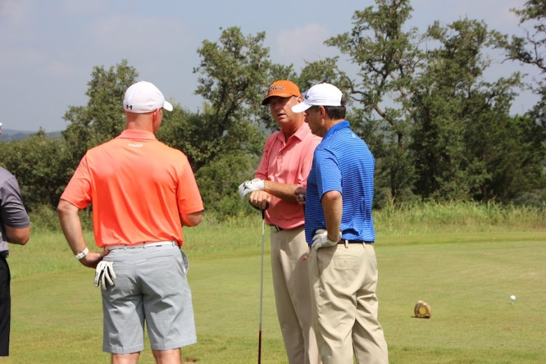 Wes Short, Jr. (center, talks with other players in his foursome before taking a swing.  Photo courtesy of Pro Link Sports.