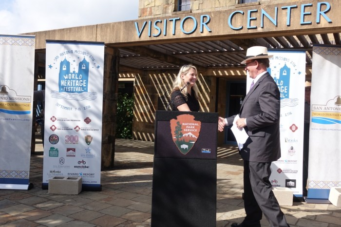 Colleen Swain, director of the City's World Heritage Office, welcomes Bexar County Judge Nelson Wolff to the podium at the World Heritage Festival kick-off.  Photo by Robert Rivard.