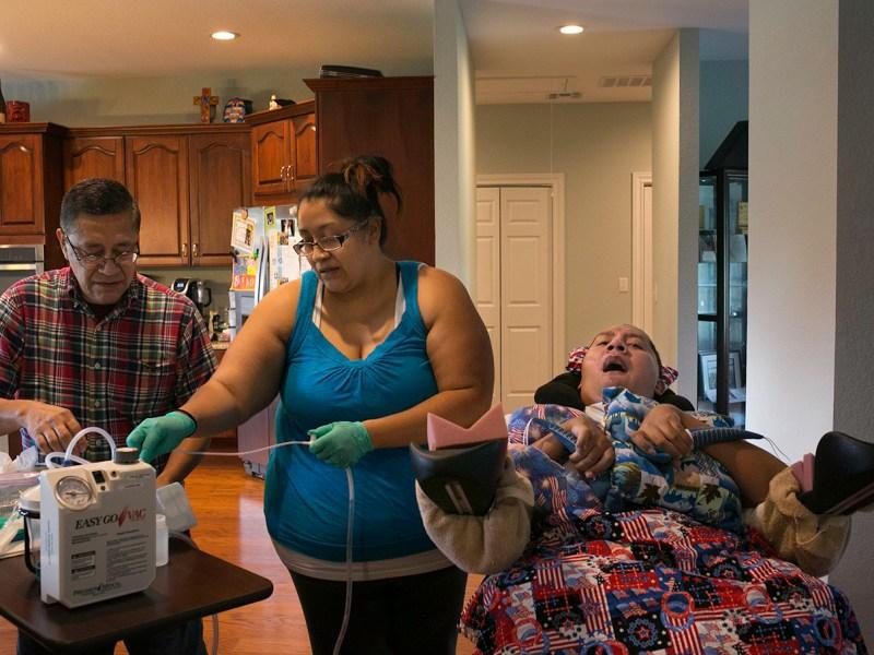 Julio and his daughter Mariana Alvarado prepare an Easy Go Vac Aspirator to help Luis Alvarado breather better. Photo by Kathryn Boyd-Batstone.