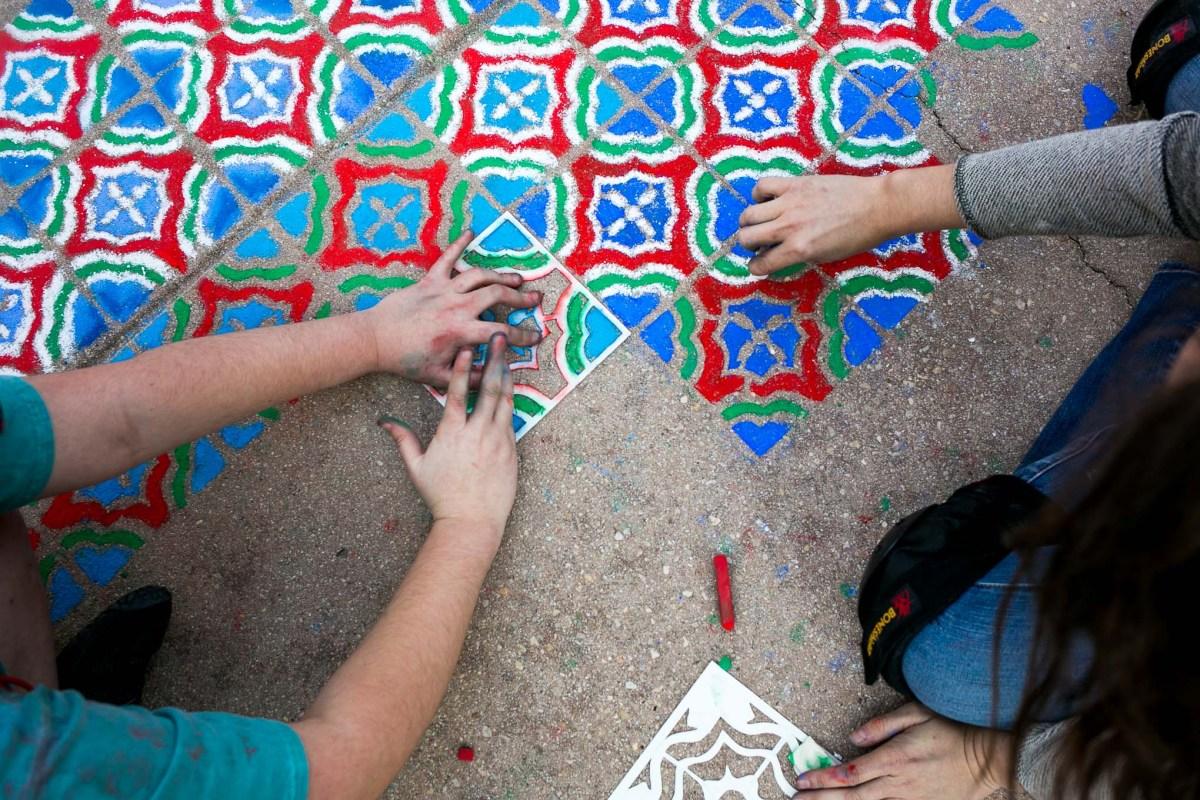 Emily Fleisher works on a stencil chalk piece. Photo by Kathryn Boyd-Batstone.