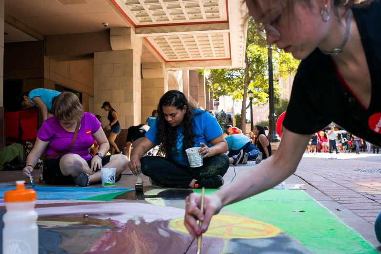 Students from Southwest School of Art work on a collaborative painting of bees and donuts. Photo by Kathryn Boyd-Batstone.