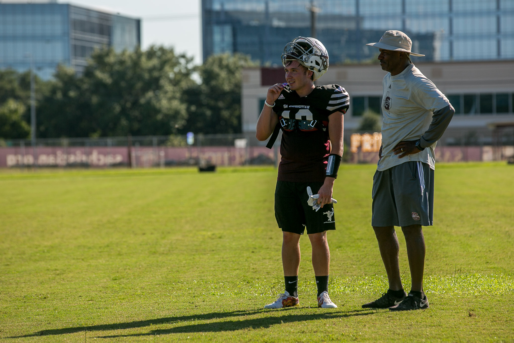 Former NFL wide receiver Henry Ellard works with a San Antonio Christian High School wide receiver during practice.