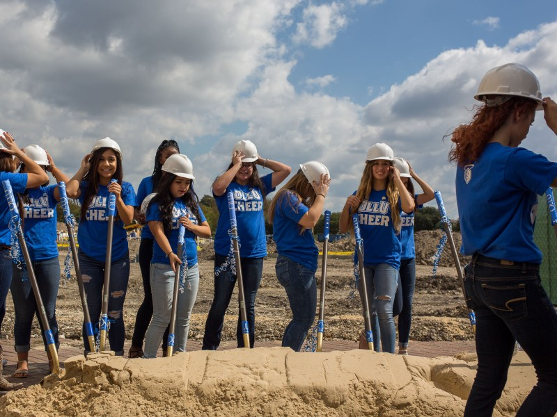 Members of Our Lady of the Lake Cheer Team prepare for a photo at the groundbreaking.