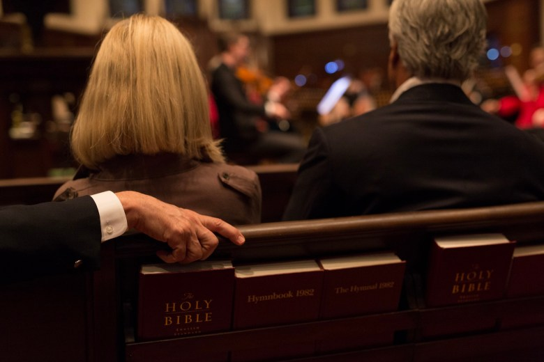 A hand of an audience member grasps a pew during the performance.