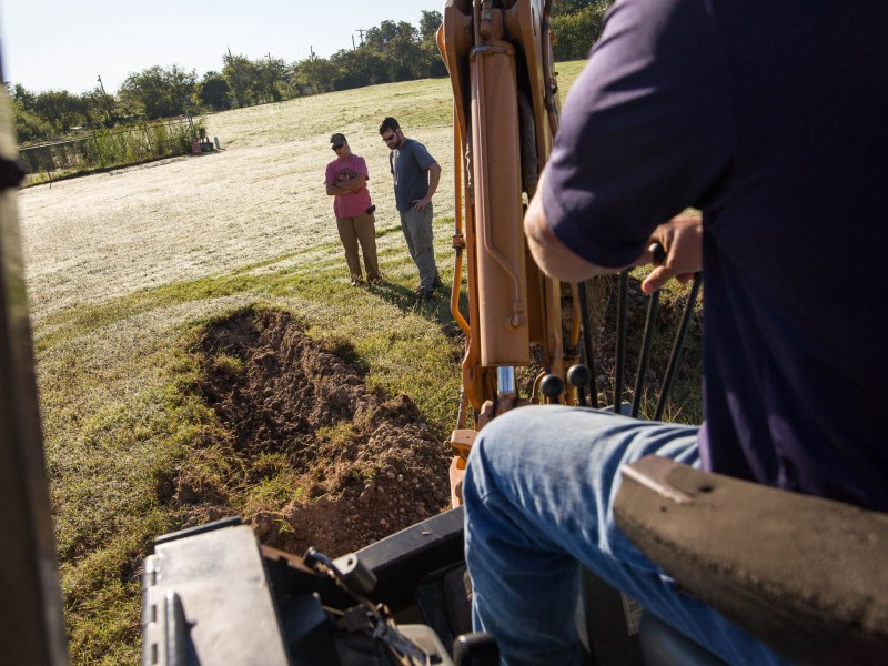 Reba Kistner Environmental employees Cyndi Dickey and Mark Luzmoor observe as backhoe operator Dean Hillman carves into the flat land where the acequia eventually was found.
