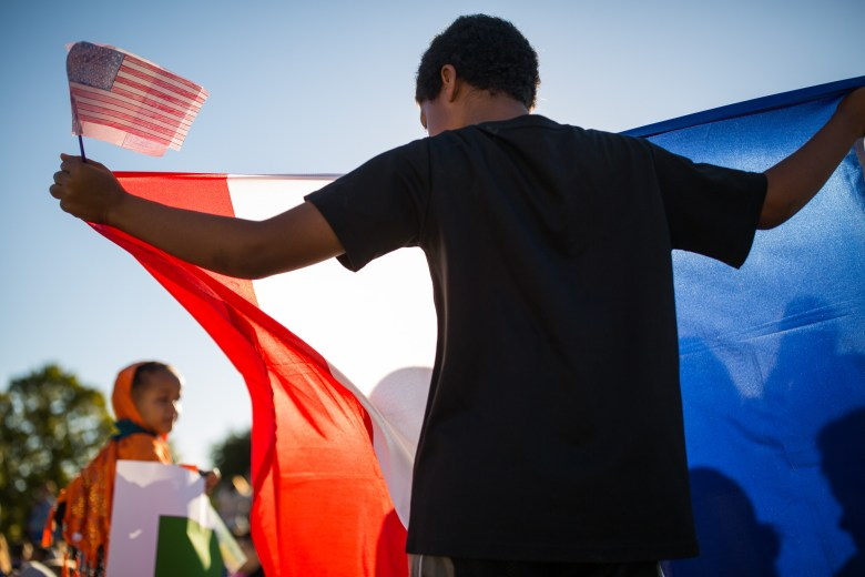 A student holds up the flag of France his county of origin.