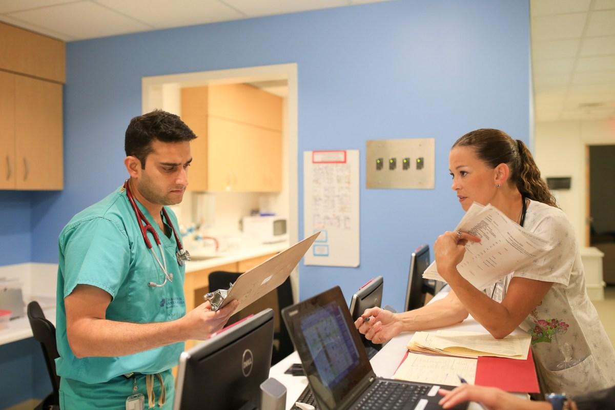 Doctor Srivastava Neeraj speaks with RN Melissa Feist-McCuistion regarding a patient update.
