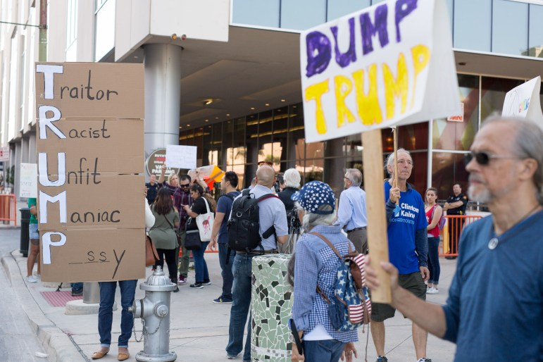 About 100 anti-Trump demonstrators gather outside the Grand Hyatt hotel before a private Trump fundraiser.